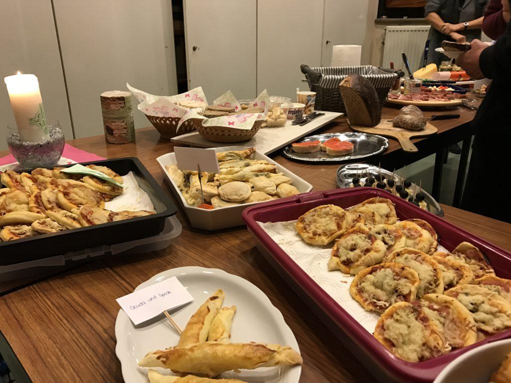 Das Foto vom Buffet beim Crossover zeigt kleine Pizzaschnitten und im Hintergrund Brot, Wurst- und Käseplatte