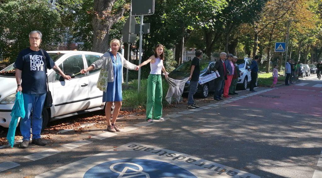 Menschen bilden eine Kette auf der Straße in dem sie sich an der Hand halten